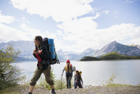 Female friends hiking with backpacks and hiking poles at remote mountain lakeside