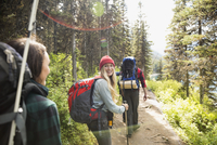 Friends hiking with backpacks and hiking poles on sunny remote trail in woods 11096044626  写真素材・ストックフォト・画像・イラスト素材 アマナイメージズ
