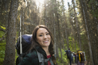 Portrait smiling woman hiking with backpack in woods