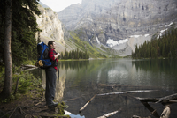 Male hiker with backpack enjoying tranquil, remote mountain lake view