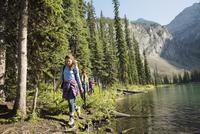 Female friends hiking along sunny remote lakeside 11096044661| 写真素材・ストックフォト・画像・イラスト素材|アマナイメージズ
