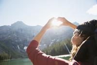 Female hiker gesturing heart-shape against sun at sunny mountain lakeside
