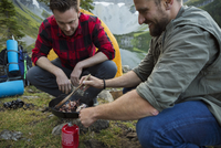 Male friends cooking bacon in skillet over kerosene camping stove at campsite