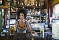 Portrait confident female bartender serving beer behind counter