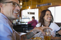 Smiling couple drinking watching game at bar