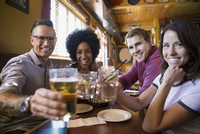 Portrait confident friends toasting beer glasses at table in bar