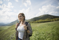 Woman with backpack hiking in remote sunny rural field