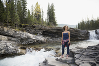 Smiling woman hiking standing at remote waterfall
