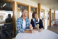 Mature couple eating ice cream cones outside ice cream shop