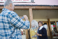 Husband photographing wife and wooden indian statue outside storefront