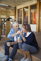 Mature couple eating sharing ice cream cones outside ice cream shop