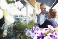 Mature couple hugging at flower shop storefront