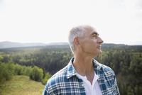 Mature man looking away on remote rural hillside 11096045140| 写真素材・ストックフォト・画像・イラスト素材|アマナイメージズ
