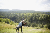 Playful mature couple hiking at sunny remote hilltop