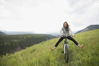 Playful woman riding mountain bike in remote rural field