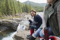 Portrait smiling woman drinking coffee from insulated drink container at waterfall