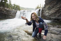 Portrait smiling woman cupping water at waterfall