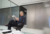 Businessman reading newspaper in office lobby 11096045243| 写真素材・ストックフォト・画像・イラスト素材|アマナイメージズ