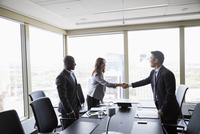 Business people handshaking in urban conference room meeting