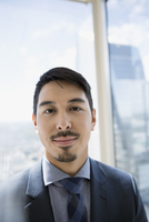 Portrait confident businessman with goatee at urban office window
