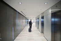 Businessman with luggage waiting for elevator in airport corridor