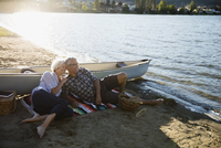 Affectionate retired couple relaxing on sunny summer lake beach
