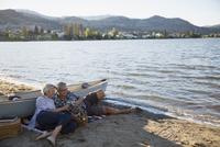 Affectionate retired couple drinking white wine on sunny summer lake beach 11096045704| 写真素材・ストックフォト・画像・イラスト素材|アマナイメージズ
