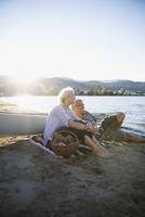 Retired couple drinking white wine on sunny summer lake beach 11096045705| 写真素材・ストックフォト・画像・イラスト素材|アマナイメージズ