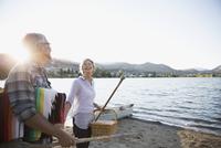 Retired couple carrying picnic basket and blanket on sunny summer lake beach 11096045706| 写真素材・ストックフォト・画像・イラスト素材|アマナイメージズ