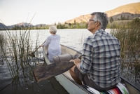 Retired couple canoeing on tranquil lake