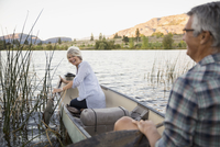 Retired couple laughing and canoeing on tranquil lake