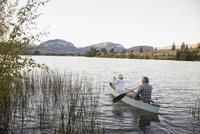 Retired couple canoeing on tranquil lake 11096045712| 写真素材・ストックフォト・画像・イラスト素材|アマナイメージズ