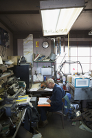 Senior male mechanic doing paperwork in workshop
