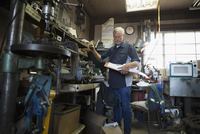 Senior male mechanic with paperwork checking inventory in workshop