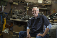 Smiling senior male mechanic in workshop