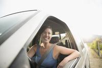 Smiling female vintner driving truck in vineyard