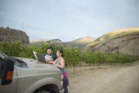 Vintners using laptop on truck in vineyard 11096045904| 写真素材・ストックフォト・画像・イラスト素材|アマナイメージズ
