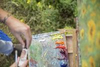 Male painter painting above multicolor palette