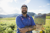 Portrait smiling male painter painting sunflowers in sunny idyllic rural field