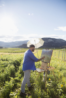 Male painter painting sunflowers in sunny idyllic rural field with sun shade umbrella 11096046082| 写真素材・ストックフォト・画像・イラスト素材|アマナイメージズ