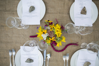 Overhead view of menus under rocks on table at harvest dinner placesetting
