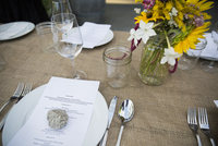 Menu under rock on table at harvest dinner placesetting