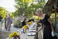 Waitress preparing harvest dinner placesettings on long patio table 11096046174| 写真素材・ストックフォト・画像・イラスト素材|アマナイメージズ