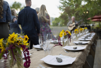 Menus under rocks at placesettings on long patio table at harvest dinner party