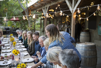 Woman serving guests at outdoor harvest dinner at long table under string lights