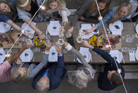 Overhead view friends toasting wine glasses at outdoor harvest dinner party