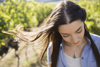 Wind blowing hair of brunette woman looking down in sunny vineyard 11096046320| 写真素材・ストックフォト・画像・イラスト素材|アマナイメージズ