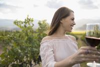 Smiling woman wine tasting drinking red wine in vineyard