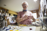 Smiling senior woman artist preparing paint in art studio