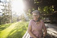 Smiling senior woman looking away on sunny, idyllic patio